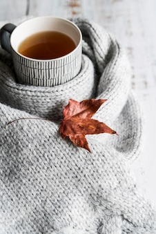 Drink with gray scarf and dry leaf