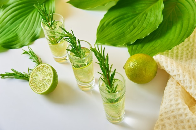Drink with lime and rosemary on table