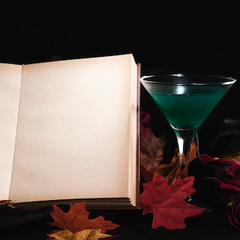 Drink with open book on black background