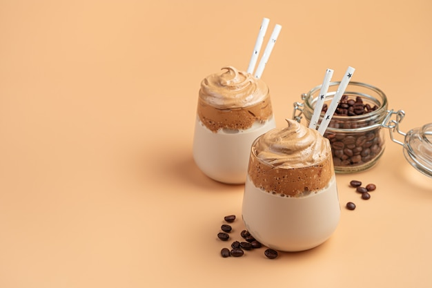 Напиток со взбитой кофейной пеной и молоком на оранжевой стене. кофе далгона. вид сбоку, копия пространства.