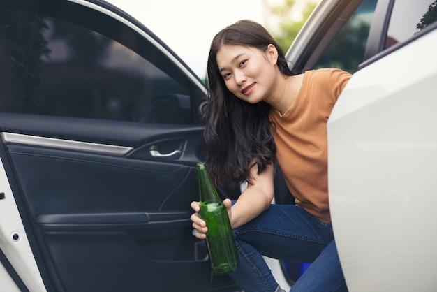 車の中でボトルからビールを飲み、女の子はアルコールを飲みます