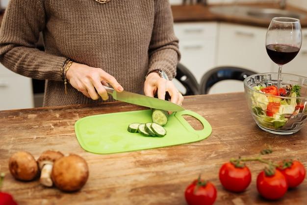 一人でお酒を飲む。夕食の準備中に台所のテーブルでキュウリを刻むベージュのセーターの正確なハンサムな女性