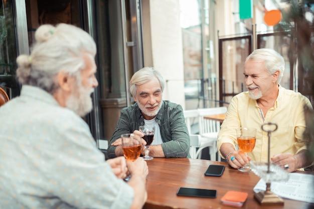 술을 마시고 이야기를 합니다. 술을 마시고 저녁에 이야기하는 수염 난 백발 남자