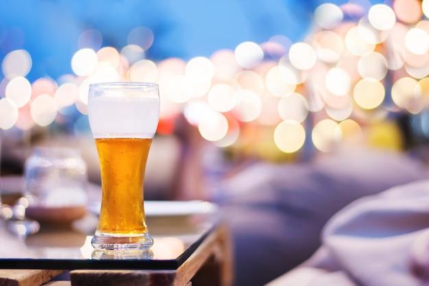 サマーナイトパーティーまたはイベントコンセプトでの飲酒アルコール。テーブル、ビール、ガラス
