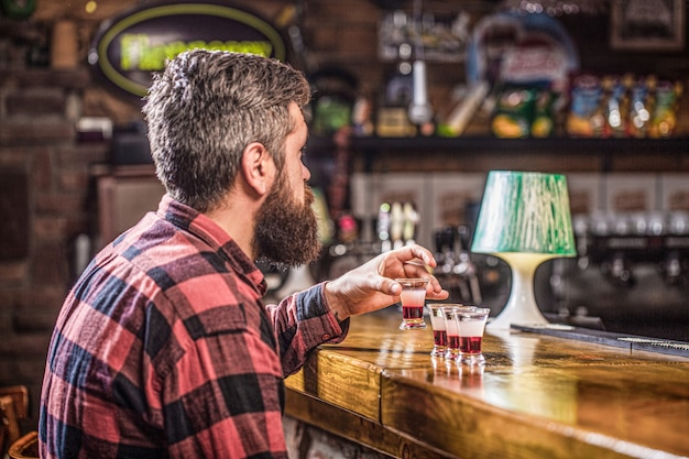 Drinking alcohol into shot glasses in a nightclub or bar. bearded man shots cocktail. tequila shots, vodka,whisky, rum. barman in pub. tequila shot. colorful cocktails at the bar.