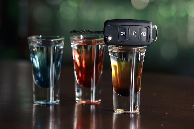 음주 및 운전 개념. 나무 테이블, 술집 배경에 자동차 키