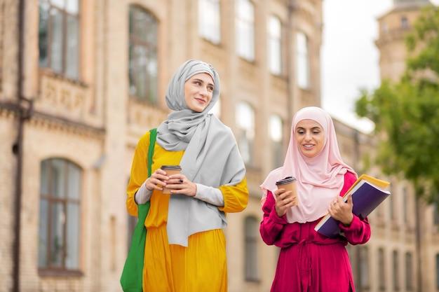 음주와 걷기. 밝은 히잡을 입고 커피를 마시고 대학에 걸어가는 무슬림 학생들