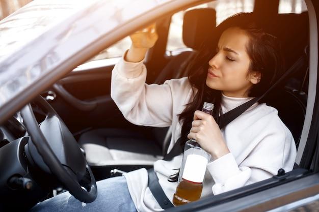 Пить за рулем. пьяная женщина водит машину.