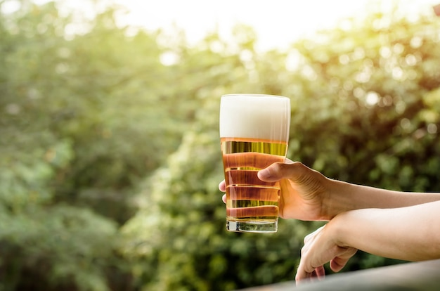 Drinking beer in summer concept. woman with glass of beer on balcony