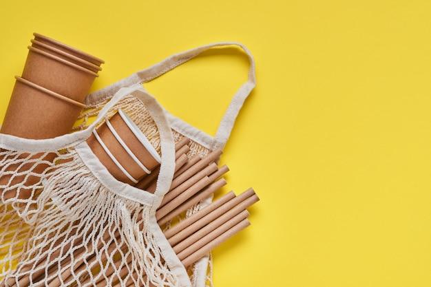 トレンディな灰色と黄色の背景に紙とコーンスターチで作られた茶色のチューブストロー、メッシュマーケットバッグ、空の紙のコーヒーカップを飲みます。ゼロウェイストとプラスチックフリーのコンセプト。上面図。