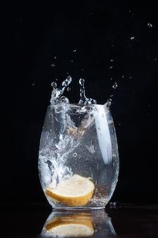 Питьевая газированная вода. движение капель лимона и цитрусовых в прозрачное стекло. брызги летят размыто.