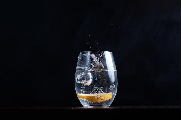 炭酸水の動きを飲むと、レモンの柑橘類が透明なグラスに落ちます