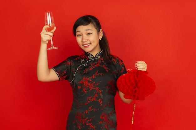 シャンパンを飲み、提灯を持っています。ハッピーチャイニーズニューイヤー2020。赤い背景の上のアジアの若い女の子の肖像画。伝統的な服を着た女性モデルは幸せそうに見えます。お祝い、感情。コピースペース。