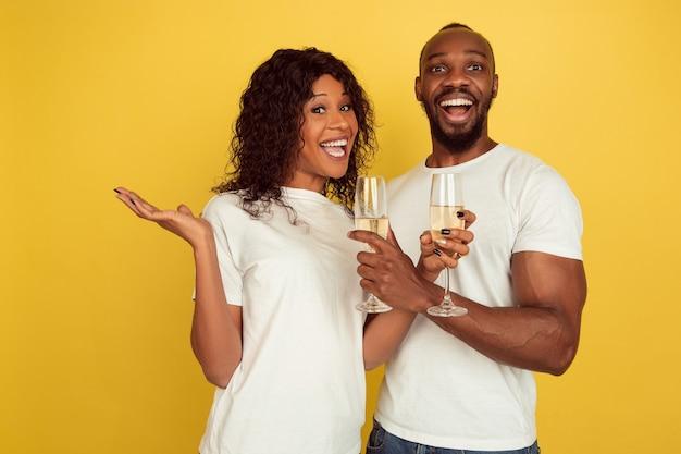 シャンパンを飲む。バレンタインデーのお祝い、黄色のスタジオの背景に分離された幸せなアフリカ系アメリカ人のカップル。人間の感情、顔の表情、愛、関係、ロマンチックな休日の概念。
