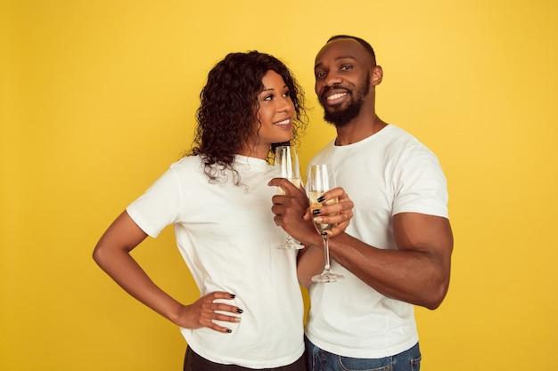 Bere champagne. celebrazione di san valentino, felice coppia afro-americana isolata su sfondo giallo studio. concetto di emozioni umane, espressione facciale, amore, relazioni, vacanze romantiche.