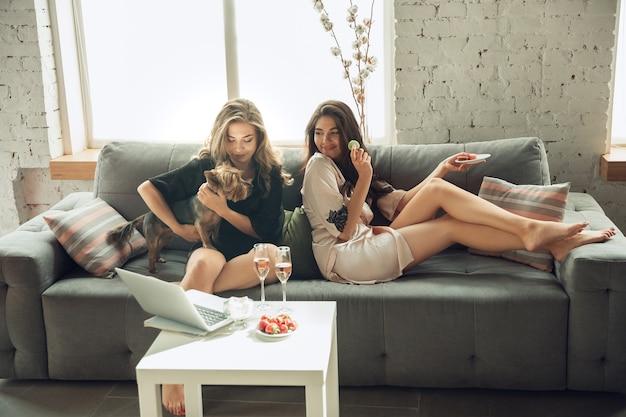 Пить шампанское с миндальным печеньем. кавказские молодые девушки, друзья, наслаждающиеся выходными, девичник вместе. выглядите мило, счастливо, весело. понятие дружбы, благополучия, образа жизни. искренние эмоции.