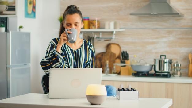 커피를 마시고 부엌에서 아로마 에센셜 오일 디퓨저로 작업합니다. 아로마 헬스 에센스, 웰니스 아로마테라피 홈스파 향 고요한 테라피, 테라피 스팀, 멘탈헬스