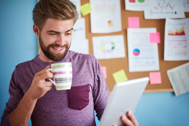 커피를 마시고 디지털 태블릿을 탐색