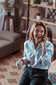 コーヒーを飲んでいる。コーヒーを飲みながら夫に電話する金髪の熟女