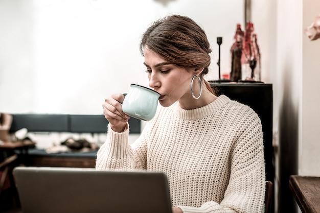 에너지를 유지하기 위해 커피를 마시고 원격으로 일하면서 커피를 마시는 여성