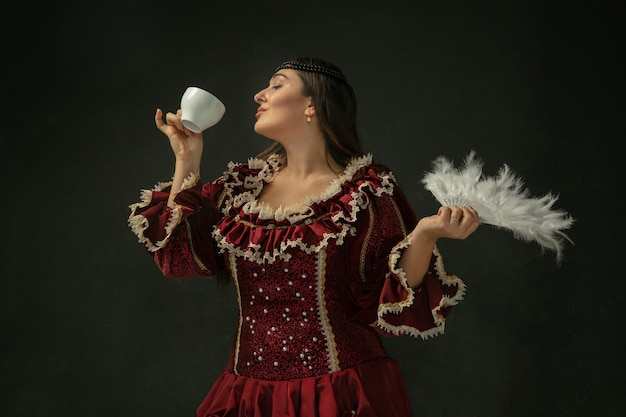 Drinking coffee, holds fluffy fan. medieval young woman in red vintage clothing on dark background. female model as a duchess, royal person. concept of comparison of eras, modern, fashion, beauty.