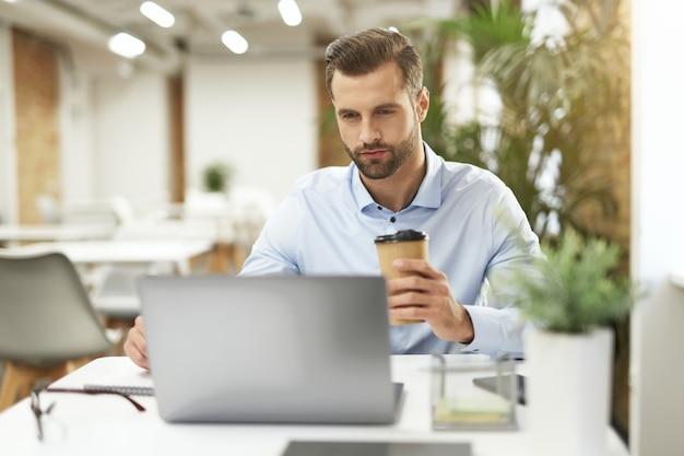 텅 빈 사무실에서 혼자 일하면서 커피를 마시며