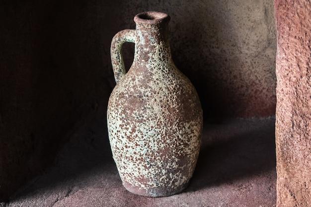Drinking earthenware jug on stone shelf indoors.