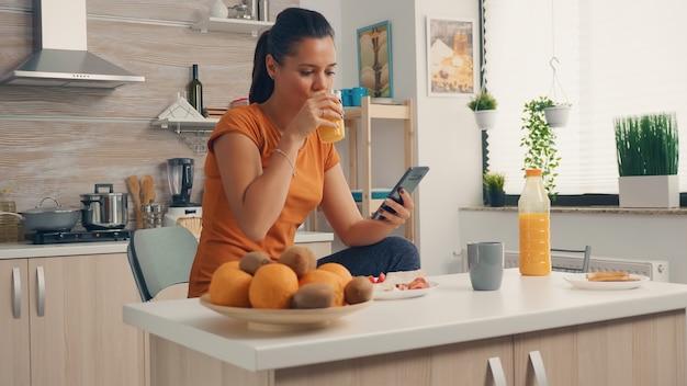 Пьет свежий апельсиновый сок и просматривает страницы на смартфоне во время завтрака. домохозяйка использует современные технологии и пьет здоровый, натуральный домашний апельсиновый сок. освежающее утро