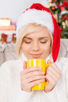 뜨거운 커피를 마시고 있습니다. 컵을 들고 눈을 감고 크리스마스 모자에 아름 다운 젊은 여자