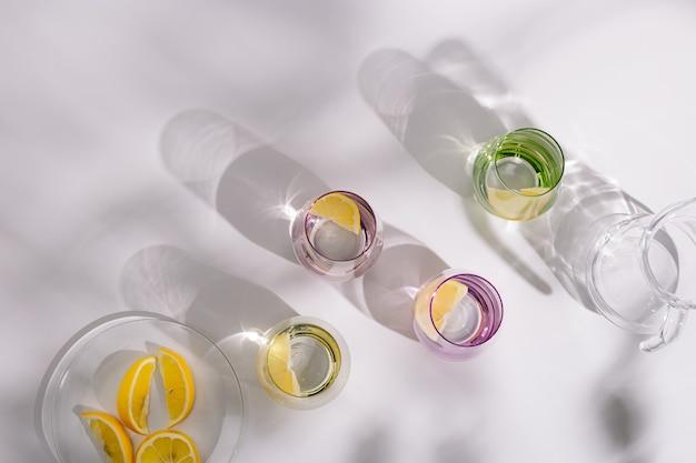 레몬 슬라이스와 함께 컬러 유리 잔에 천연 물을 마시기