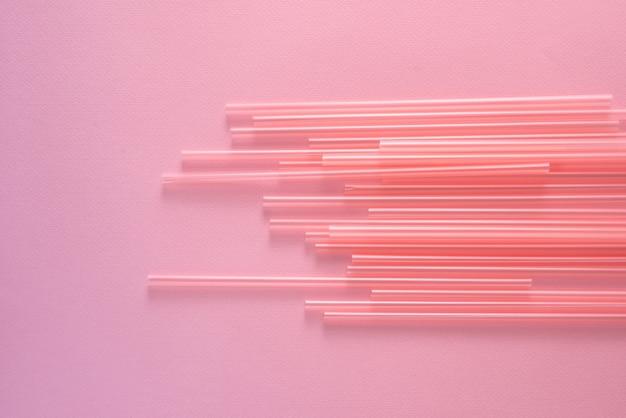 明るいピンクの背景、上面図でストローを飲む