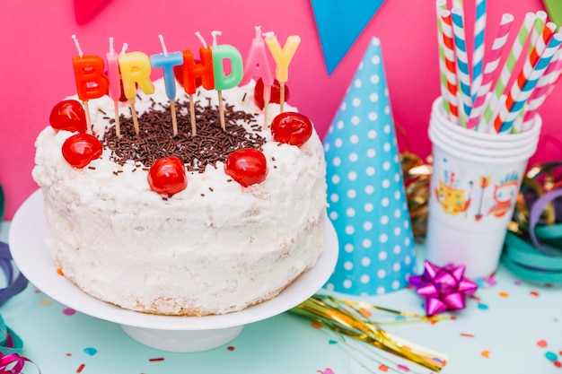 Drinking straws; party hat and birthday cake on cake stand