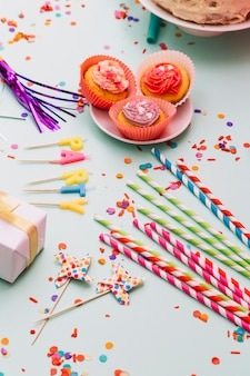 Drinking straws; prop; candles; cupcake; gift box; and confetti on blue background