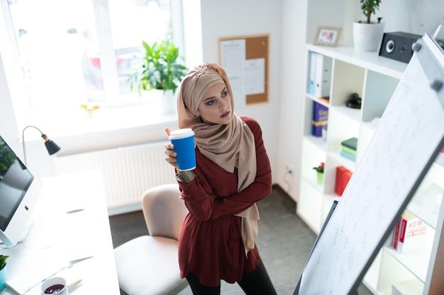 持ち帰り用のコーヒーを飲む。テイクアウトのコーヒーを飲み、ホワイトボードを見ている若いイスラム教徒の教師