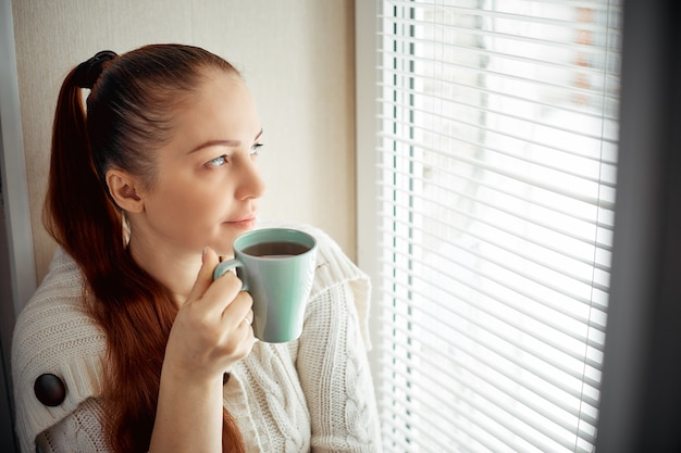 Drinking tea sitting on the window of caucasian beautiful middle-aged woman with red hair.