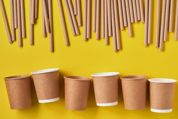 Трубки для питья из бумаги и кукурузного крахмала, биоразлагаемого материала и стаканы из эко-бумаги на фоне желтого тренда 2021 года. концепция без отходов и без пластика. вид сверху.