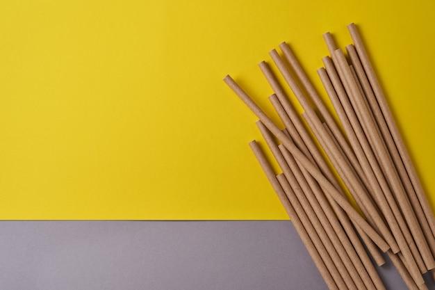 Трубки для питья из бумаги и кукурузного крахмала, биоразлагаемого материала на желтом цветном фоне 2021 года. концепция без отходов и без пластика. вид сверху.