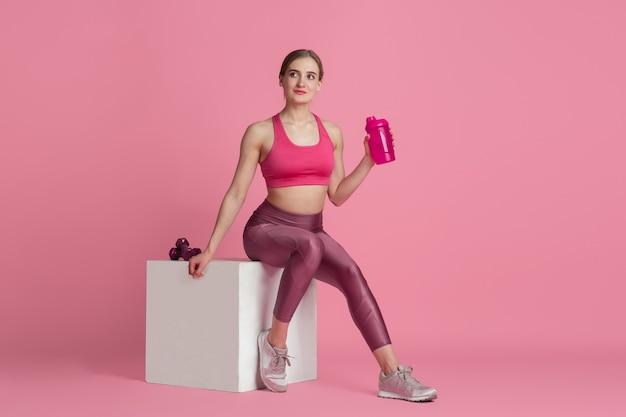 식수. 스튜디오, 단색 핑크 초상화에서 연습하는 아름 다운 젊은 여자 선수