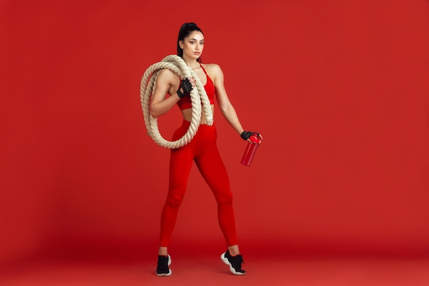 Drinking water. beautiful young female athlete practicing in , monochrome red portrait. sportive fit brunette model with ropes. body building, healthy lifestyle, beauty and action concept.