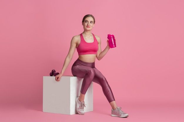 Drinking water. beautiful young female athlete practicing in studio, monochrome pink portrait