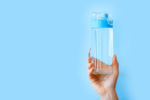Бутылка питьевой воды для спорта в женской руке на синем backgraund с копией пространства. многоразовая бутылка. концепция здорового образа жизни и фитнеса.