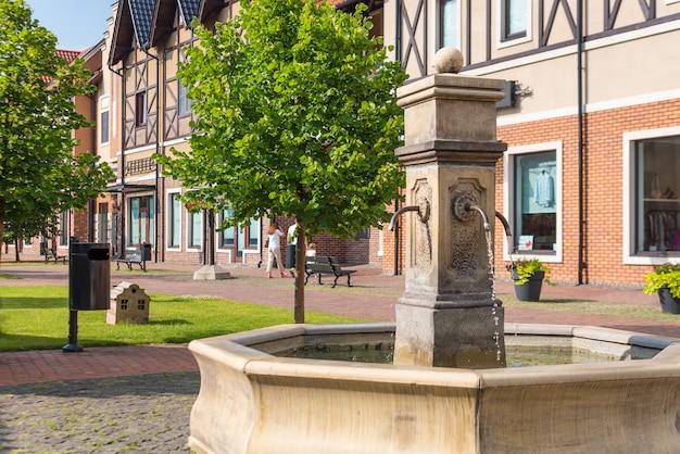 Фонтан питьевой воды на пешеходной улице в небольшом европейском городе