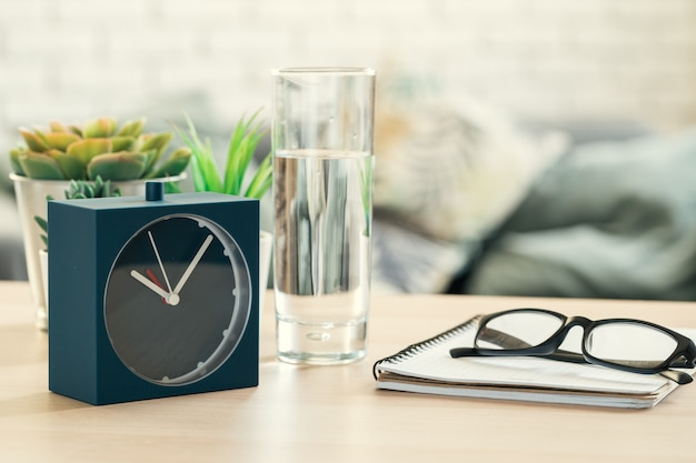 Drinking water health concept. alarm clock and glass of water on table