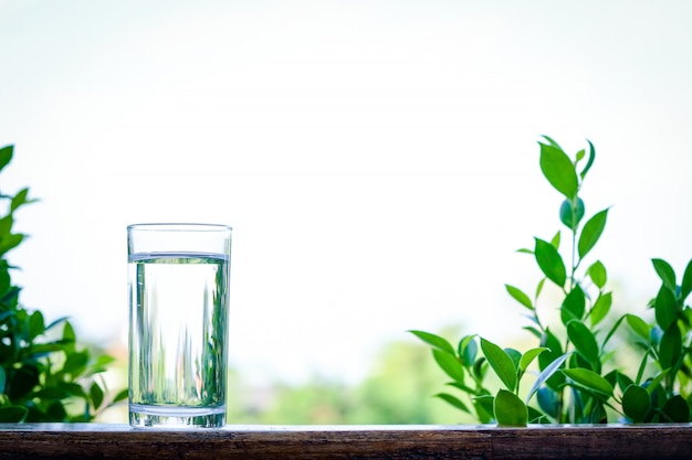 Drinking water is in a clear glass placed on a wooden floor with a free space on top.