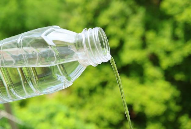 Питьевая вода льется из пластиковой бутылки на фоне зеленой листвы