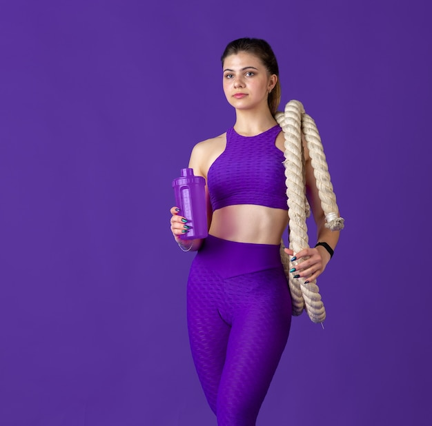 Drinking water with bottle. beautiful young female athlete practicing , monochrome purple portrait. sportive fit model with ropes. body building, healthy lifestyle, beauty and action concept.