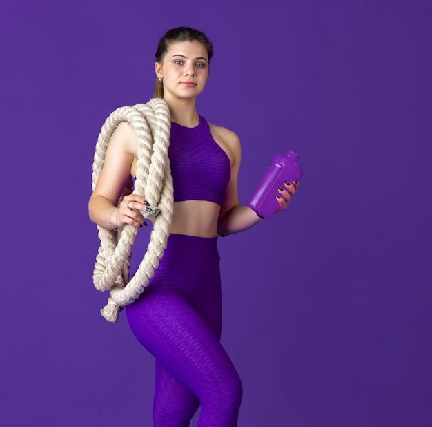 Drinking water with bottle. beautiful young female athlete practicing in studio, monochrome purple portrait.