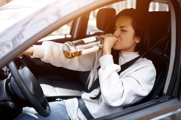 Drinking at the wheel. a drunk woman drives a car.
