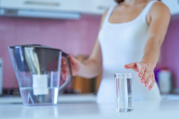 Питьевая женщина пьет чистую очищенную воду из водяного фильтра утром на кухне дома