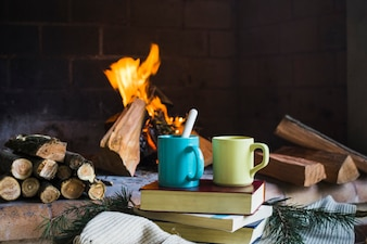 Drinks and books near flaming fireplace